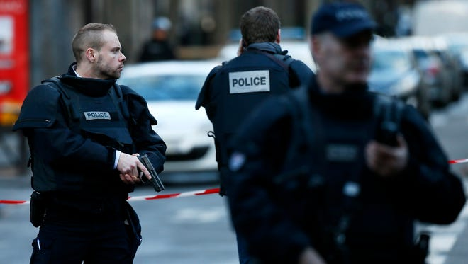 Police officers stand guard near a shooting scene after a man carrying a knife attempted to enter a Paris police station in the Goutte d'Or area, northern Paris on Jan. 7, 2016.