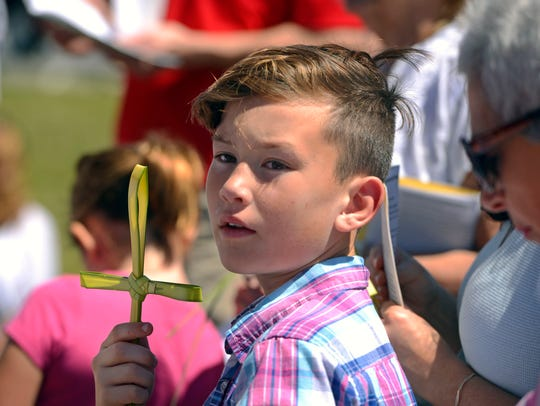Nathan Weber participates in the Palm Sunday Stations of the Cross procession in Gulf Breeze last year.