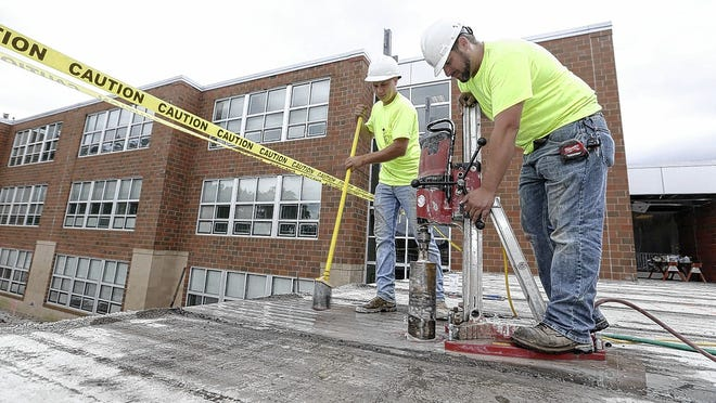 Shane Bills (left) and Jarrod Godfrey with Ohio Plumbing Electrical Inc. of Celina work on the addition to Rosemore Middle School.