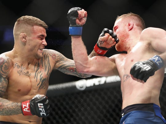 Justin Gaethje (R) throws a punch at Dustin Poirier