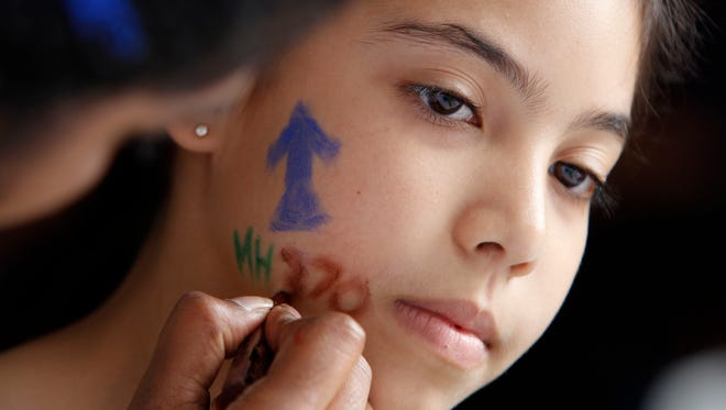 A girl has her face painted during the Day of Remembrance for MH370 event in Kuala Lumpur, Malaysia on Saturday, March 4, 2017.