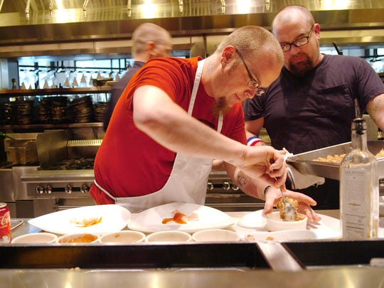"Chef Shannon Yates, left, and sous chef Heath Higginbotham plate entrees of grilled New Zealand elk loin with ""Crushed Potatoes"" flavored with fig vinegar, fennel, onion and toasted garlic at Cru restaurant in December 2006."