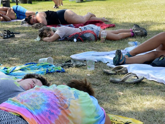 Festival goers take naps in the shade, a chance to