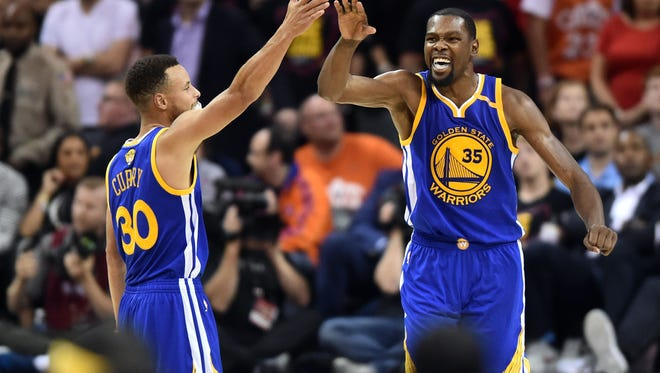 Golden State Warriors guard Stephen Curry (30) and forward Kevin Durant (35) celebrate during the fourth quarter against the Cleveland Cavaliers in game three of the 2017 NBA Finals at Quicken Loans Arena.