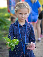 Anika Nelson, 9, holds some of the herbs she harvested