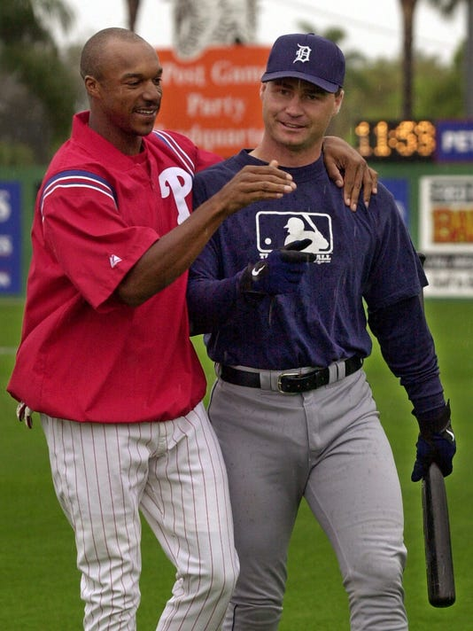 FILE - In this March 4, 2001, file photo, Philadelphia Phillies outfielder Brian L. Hunter, left, greets Detroit Tigers catcher Scott Servais as they walk across the rain-soaked outfield at Jack Russell Stadium in Clearwater Fla. The Seattle Mariners have hired former major league catcher Scott Servais as their manager. New Mariners general manager Jerry Dipoto made the announcement Friday, Oct. 23, 2015. Servais replaces Lloyd McClendon, who was let go earlier this month.(AP Photo/Kathy Willens, File)