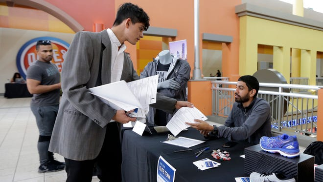 In this Tuesday, Oct. 3, 2017, photo, job seeker Gustavo Cano, left, hands his resume to Javier Torres at a job fair at the Dolphin Mall in Sweetwater, Fla. On Thursday, Oct. 26, 2017, the Labor Department reports on the number of people who applied for unemployment benefits the week before.