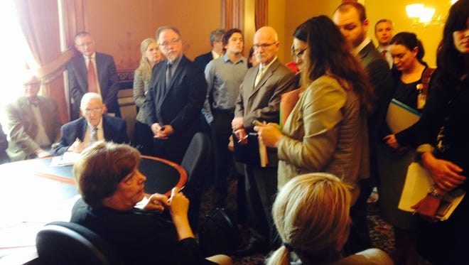 Rep. Linda Miller, seated lower left, is surrounded by lobbyists Wednesday during a subcommittee meeting about a bill related to the impending shift to private managed care of the state's $4 billion Medicaid program.