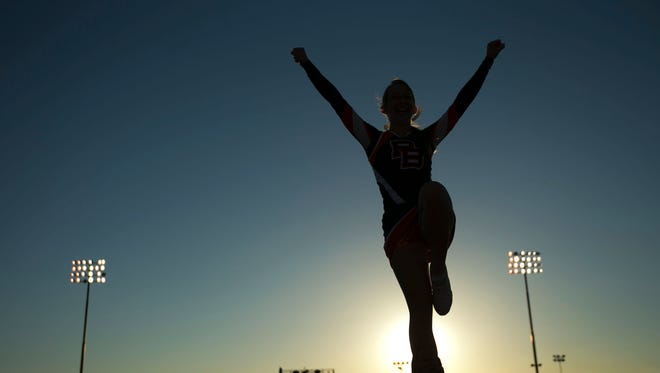 The Poston Butte cheerleaders perform a stunt before the high school football game against Queen Creek High on Friday, August 22, 2014.