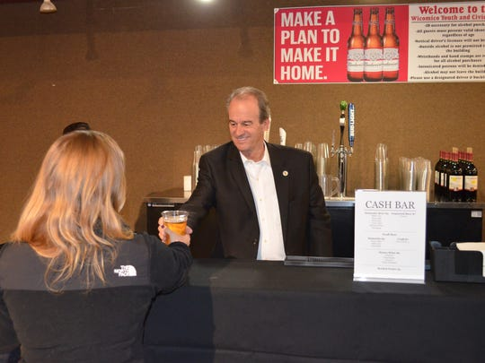 Wicomico County Executive Bob Culver pours the first alcoholic beverage  for sale at the Wicomico Youth & Civic Center on Friday, Nov. 18.