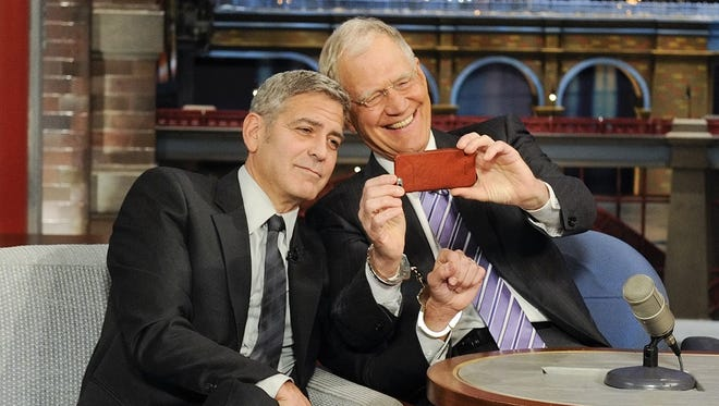"George Clooney and David Letterman share a moment during Thursday's episode of ""Late Show."""