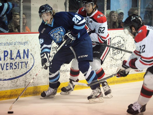 Brian Pinho of the Ice looks to pass behind the goal as he is defended by Waterloo's Brandon Montour in the first period. This is from a Clark Cup Playoffs game between the Indiana Ice and the Waterloo Black Hawks at Pan Am Plaza Friday May 16, 2014.