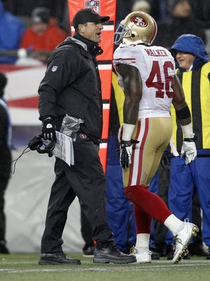 San Francisco 49ers coach Jim Harbaugh, left, congratulates tight end Delanie Walker after a touchdown against the New England Patriots.