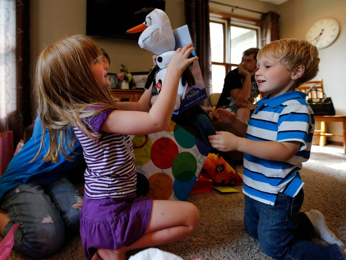Jillian Dammann opens gifts at her 7th birthday party as her little brother Jayden, 3, looks on during a birthday celebration with family and friends at Justin and Jennifer Dammann's home near Essex on July 19, 2014.