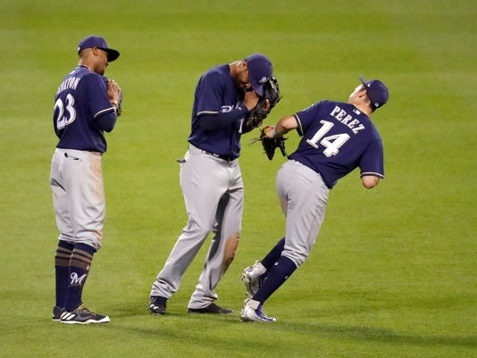 Milwaukee Brewers' Keon Broxton (23), Domingo Santana and Hernan Perez (14) celebrate following the team's baseball game against the St. Louis Cardinals, early Thursday, June 15, 2017, in St. Louis. The Brewers won 7-6. (AP Photo/Jeff Roberson)
