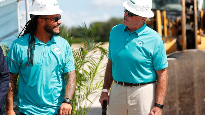 Former Miami Dolphins players Channing Crowder, left, and Kim Bokamper chat during a ground breaking ceremony for the teams new NFL football training facility, Wednesday, Aug. 21, 2019, in Miami Gardens, Fla. The Dolphins broke ground on a $135 million training complex and sports performance clinic next to Hard Rock Stadium where the team plays. (AP Photo/Wilfredo Lee)