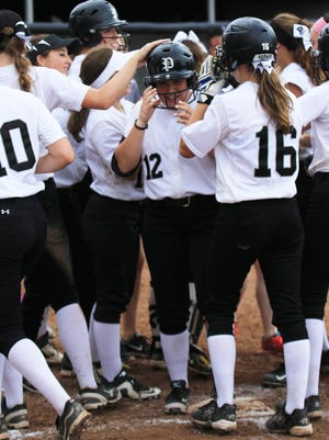 Plymouth senior Mikayela Marciniak (No. 12) is mobbed at home plate after hitting a three-run homer Saturday against Livonia Churchill.