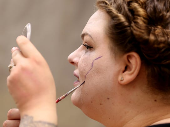 Kristina Malmberg demonstrates how to draw veins on a face during a Halloween Makeup Workshop at Chemeketa Community College in Salem.