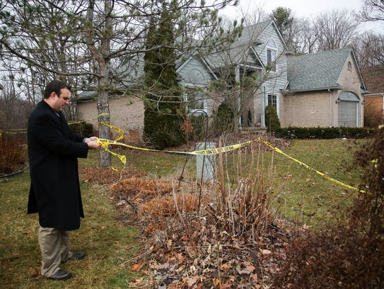 A Novi police detective secures the police tape around