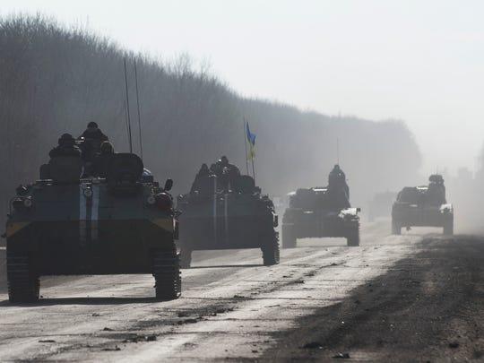 Ukrainian troops ride on armored vehicles ahead of
