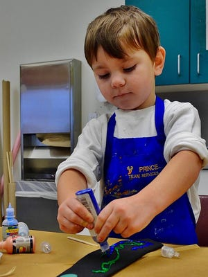 A child works on a project at the Holland Area Art Council's Sneaky Elves event. In the past, the event allowed children ages five and older to create and wrap their own handmade gifts. This year, the event will be focused on take-home boxes.