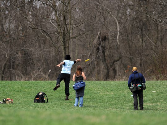 A group of people plays disc golf Monday, April 2,