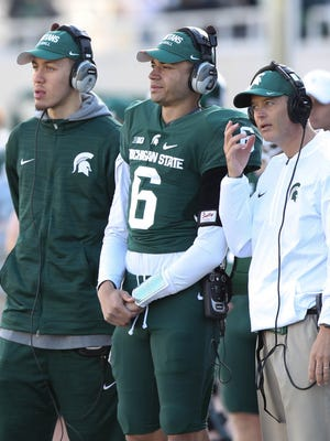 Michigan State quarterbacks Messiah deWeaver, left, Damion Terry and quarterbacks coach Brad Salem on the sideline during the spring game at Spartan Stadium, Saturday, April 1, 2017.