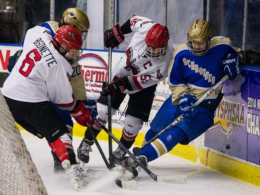 Alec DeYoung #22 (right) of Webster battles for a puck in the corner during the first period.