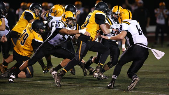 Cascade linebacker Malachi Gonzalez (56) brings down Philomath running back Trenton Looper (23) during the quarterfinals of the OSAA Class 4A state playoffs, Friday, November 13, 2015, at Corvallis High School in Corvallis, Ore.