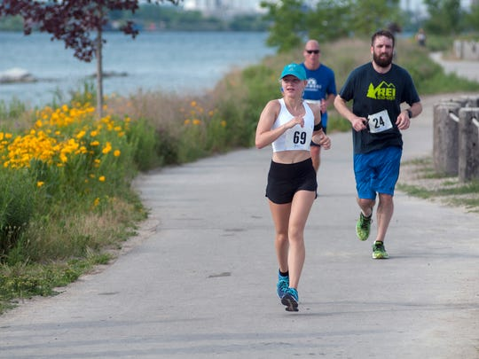 Peri Dworatzek, left, of London, ON, races along the Blue Water River Walk Sunday, June 26, during the Blue Water Half Marathon in Port Huron.
