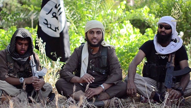 """A file image grab uploaded on June 19, 2014, by Al-Hayat Media Centre shows 21-year-old British citizen Reyaad Khan (left), 20-year-old British citizen Abu Muthanna al-Yemeni, center, believed to be Nasser Muthana, and 26 year-old British citizen Ruhul Amin, right, in an online video entitled """"There is no life without Jihad"""" from an undisclosed location. A Royal Air Force drone killed British jihadists Khan and Amin in Syria in August."""
