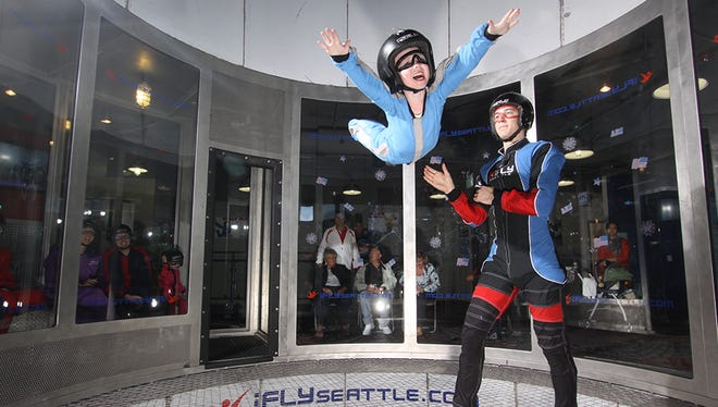 Kids can fly! A child flies at iFLY Seattle as her instructor spots her. iFLY an indoor skydiving venue, will open in Ridge Hill in 2016.
