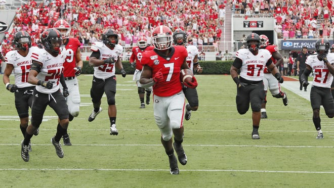 Georgia running back D'Andre Swift (7) scores on a pass play which he broke for a touchdown during the first half of an NCAA college football game against Arkansas State, in Athens, Ga. on Sept. 14, 2019. A team can go on the road and play a Power Five conference team and earn $1 million-$2 million, often enough to keep other sports programs afloat or fund the training table or academic center.