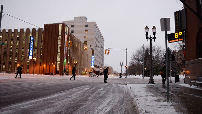 Pedistrians cross Allegan Street at Capitol Avenue as the Boji Tower marquee displays the temperature Friday, January 9, 2015.