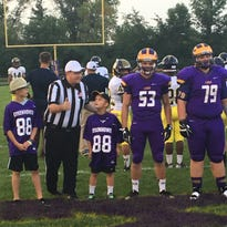 New Berlin Eisenhower's Jaron Radish (53) is joined at midfield by his younger brothers, Jude and Jaxson, prior to a game against Pius XI on Sept. 9.