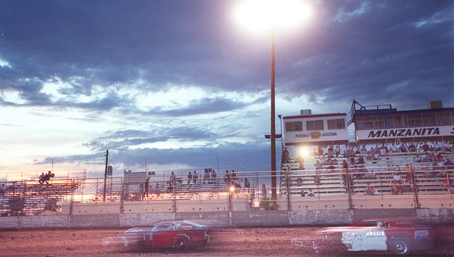 Stock cars race around the track at Manzanita Speedway as the sun sets behind the stands in this 2001 photo. The track closed in 2009.
