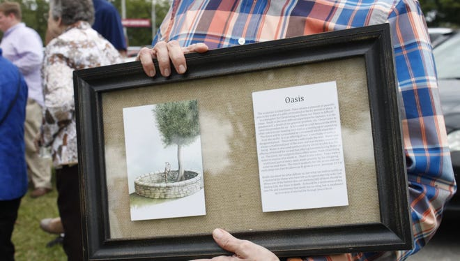 "Olivia Greenlee's father, Barry, holds a commemorative plaque given to him and his wife Saturday at the dedication of the ""Oasis"" memorial."