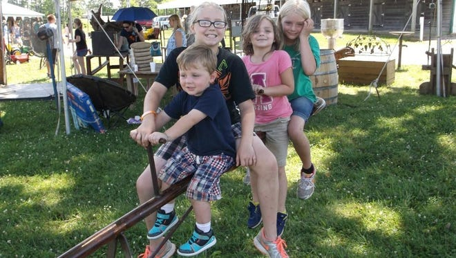 The Morrow siblings – Jake, 2; Lexi, 10; Listi, 8; and Ali, 8 – play on their father's repurposed teeter-totter, constructed from an oil drilling pipe, a wagon wheel and tractor seats, selling for $400 at the June 21 Burlington Antiques Show. Hailing from Crossville, Tennessee, the Morrow family has been buying and selling antiques for four years.