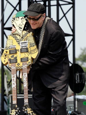 """Rick Nielsen holds his trademark guitar, """"Uncle Dick,""""  at the Virgin Festival in Baltimore."""