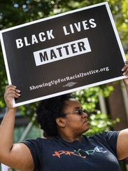 A woman holding a Black Lives Matter poster at a Louisville