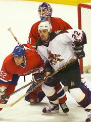 Coyotes right wing Rick Tocchet tries to hold his ground
