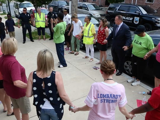 Wilmington Police Chief Robert Tracy and other officers, as well as teachers and students from Lombardy Elementary School, pray with members of Safe United Neighborhoods before a regularly scheduled neighborhood walkabout Friday.