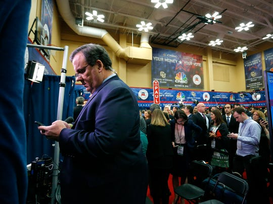 Chris Christie, left, checks his phone in the spin