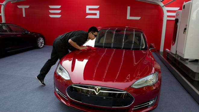 A worker cleans a Tesla Model S sedan before an event to deliver the first set of cars to customers in Beijing.