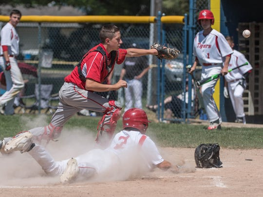 St. Philips's Ryan Reincke dives into home plate for