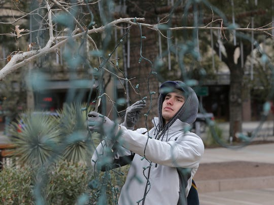 Jesus Reyes bundles up as he helps remove Christmas lights from San Jacinto Plaza Tuesday afternoon. Temperatures in El Paso dipped into and remained in the high 30s for much of the day.