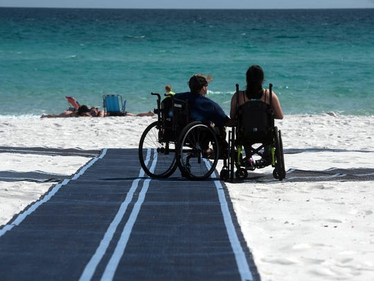 John Wood and Brianna Tran use the Mobi-Mats at Navarre Beach to get close to the shoreline March 28, 2018. Mobi-Mats were recently installed on Pensacola Beach at both Casino Beach and Quietwater Beach.
