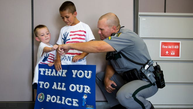 Gavin Harhen, 3, left, gives Mark Long a fist bump while his brother Grant Harhen, 6, smiles on July 22, 2016. The boys delivered cookies to the Collier County Sheriff's Office to thank them for their service.