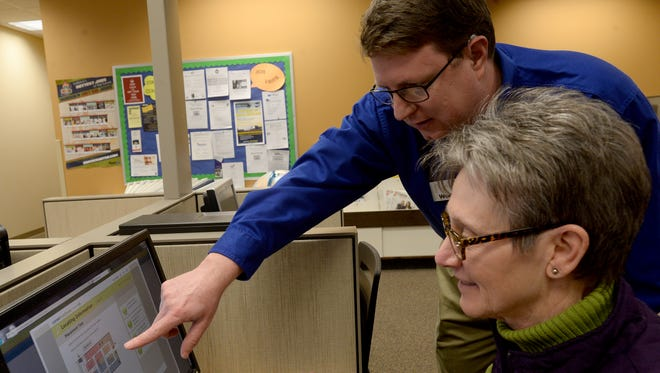 Darren Roberts and Patty Kelley look at the WorkKeys testing website at WorkOne's office in Richmond.