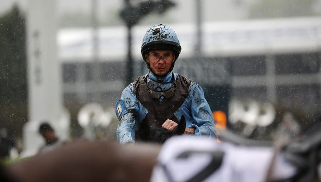 Covered in mud, jockeys head back for their next race at Churchill Downs on May 5, 2018.